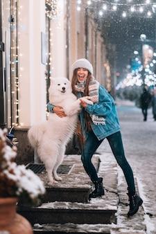 Женщина обнимает свою собаку на ночной улице