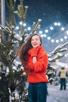Молодая женщина позирует возле елки на улице