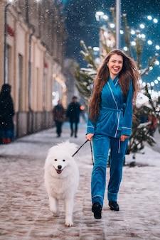 白い犬と一緒に歩いている女性