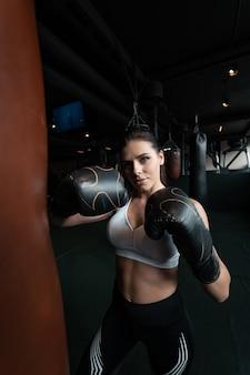 ボクシング女性がサンドバッグでポーズします。強くて独立した女性の概念