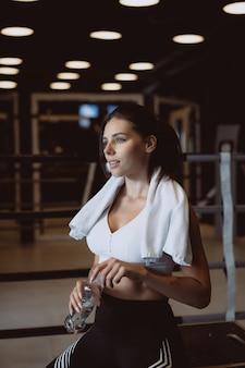 Великолепная молодая женщина с полотенцем на плечах открывает бутылку с водой в тренажерном зале