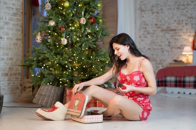 Красивая молодая женщина с подарками на елке