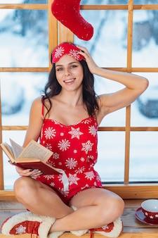 Красивая молодая брюнетка женщина в красной пижаме и чтения у окна
