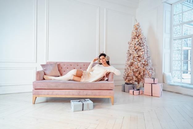 クリスマスの時期にソファの上の白いドレスの若い女性