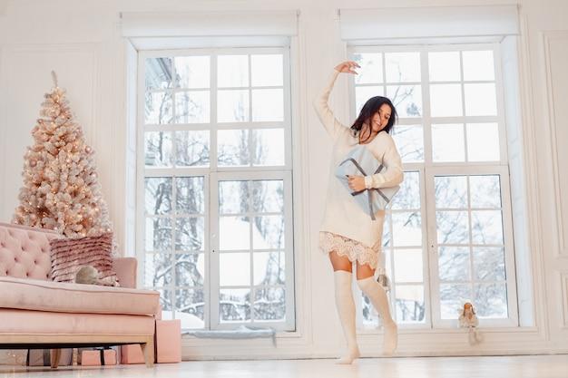 Красивая молодая женщина в белом платье позирует с подарочной коробке