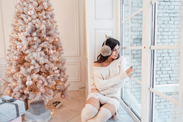 クリスマスツリーの近くのエレガントなドレスの若い女性