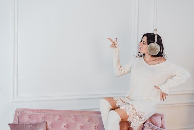 部屋でポーズをとって白いドレスの若い女性