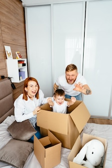 Папа, мама и маленький сын играют в спальне с бумажными коробками