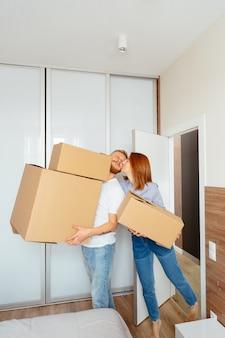 幸せなカップルの段ボール箱を押しながら新しい場所に移動