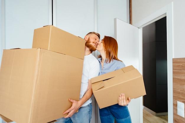 Счастливая пара держит картонные коробки и переезжает на новое место