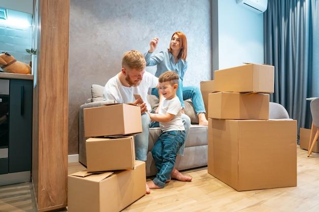 Молодая счастливая семья с ребенком, распаковка коробок вместе сидя на диване