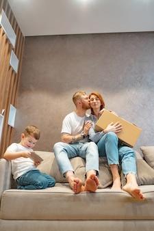 ソファの上に座って一緒に箱を開ける子供と若い幸せな家族