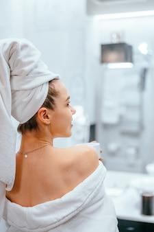 Портрет красотки красотки одевает белое банное полотенце