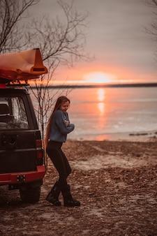 Женщина, наслаждаясь время отдыха у красивого озера на рассвете