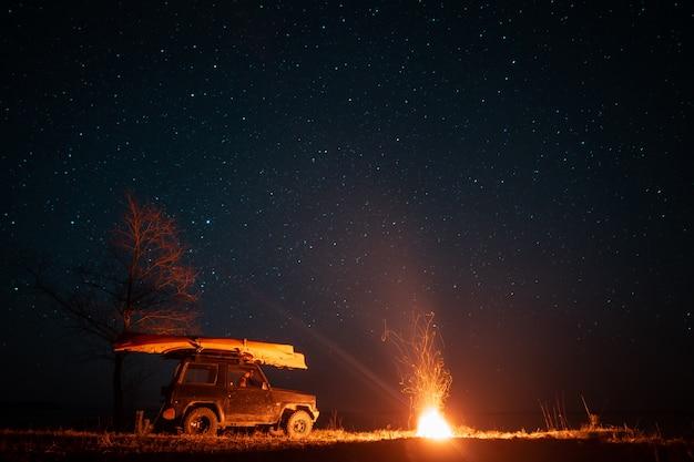 明るいキャンプファイヤーと車のある夜の風景