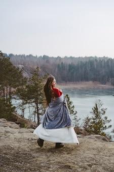 若くてきれいな女性が湖でポーズ