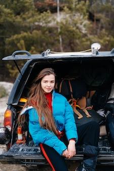 車のトランクに座って自然を楽しむ若い女性