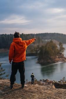 崖の端に立っていると指している若い男