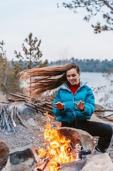 たき火の隣に座って幸せな若いブルネットの女性