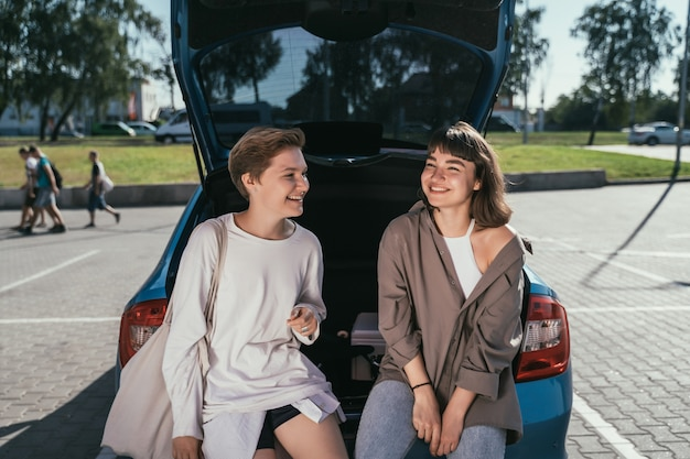 Две девушки на стоянке у открытого багажника позируют
