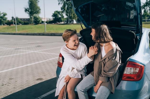 Две девушки на стоянке у открытого багажника позируют перед камерой.