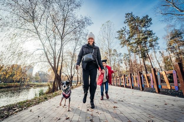 幸せな母と娘は秋の公園で犬と一緒に歩く