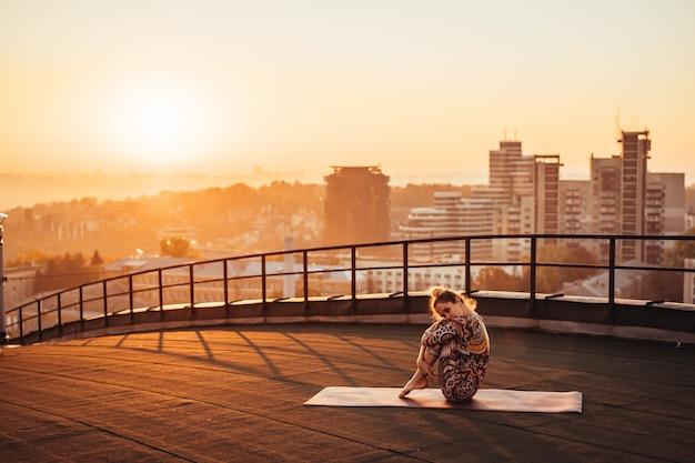 大都市の高層ビルの屋根でヨガをしている女性。