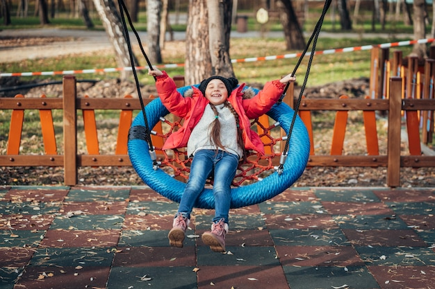 スイングで幸せな子供の女の子。秋のパックで遊ぶ子供。