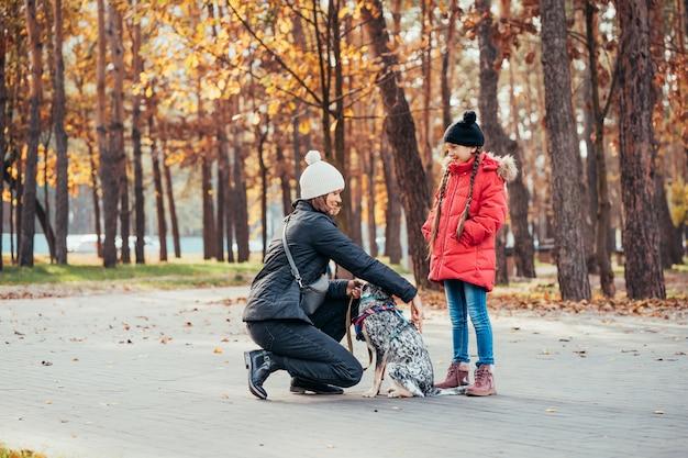 幸せな母と娘の秋の公園で犬と遊ぶ