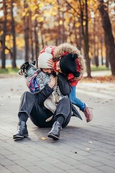 Счастливая мать и ее дочь, играя с собакой в осенний парк