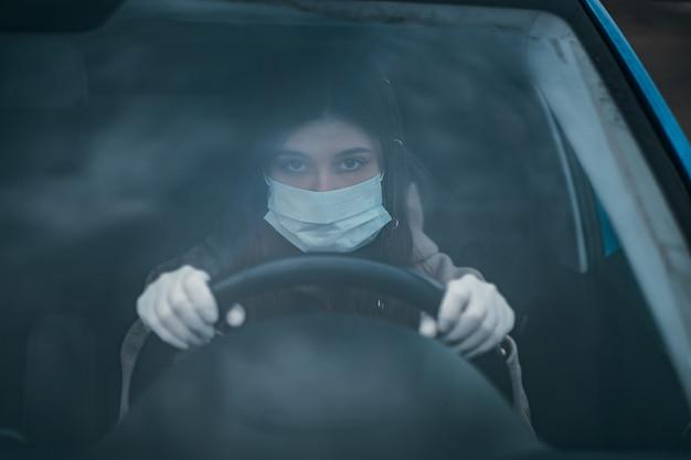 マスクと手袋をはめて車を運転する若い女性。