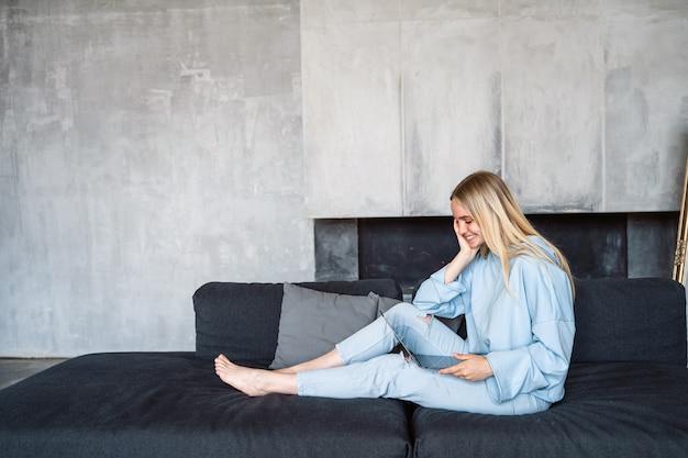 ソファーに座って銀のラップトップを使用して幸せな女
