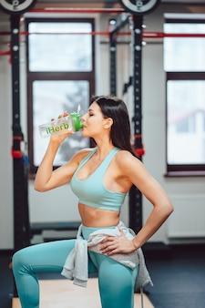 Спортсменка отдыхает и пьет воду на лестнице в тренажерном зале