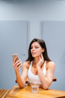 若い女性に座って、トレーニング後にスマートフォンを使用して