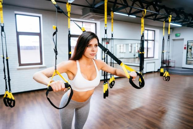 Молодая взрослая женщина делает упражнения в тренажерном зале