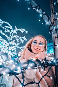 若い女性が照らされた木が付いている通りでポーズ