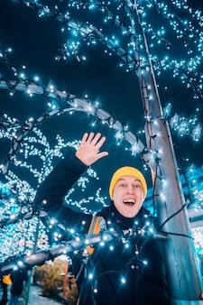 Молодой человек на улице с подсветкой деревьев