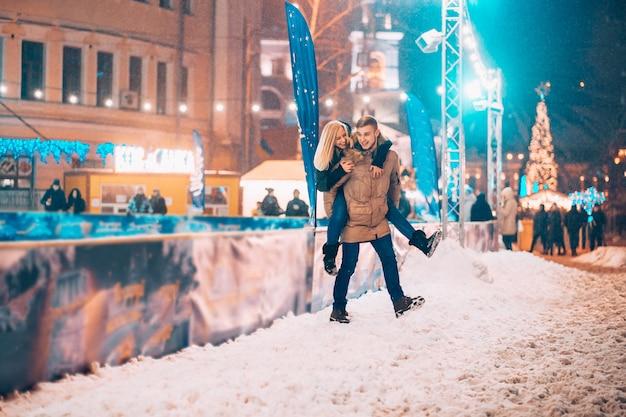 Веселая и игривая пара в теплых зимних нарядах дурачится
