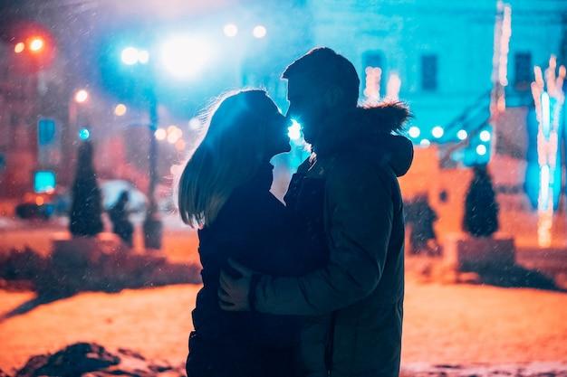 Молодая пара взрослых в объятиях друг друга на заснеженной улице