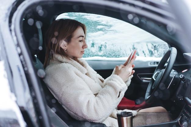 Привлекательная женщина водитель сидит за рулем в своей машине