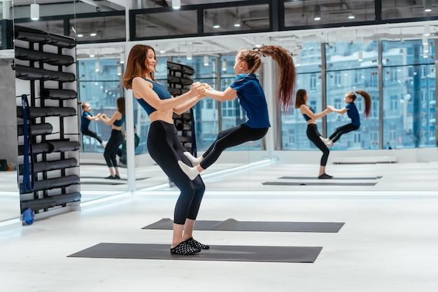 Молодая взрослая мать делает фитнес с маленькой дочерью