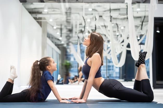 Молодая взрослая мама и маленькая дочь вместе на аэробике