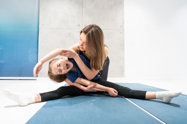 Мама и дочь делают растяжку перед тренировкой