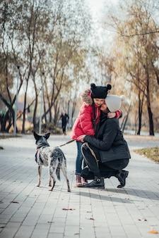 幸せな母と娘が秋の公園で犬と一緒に歩く
