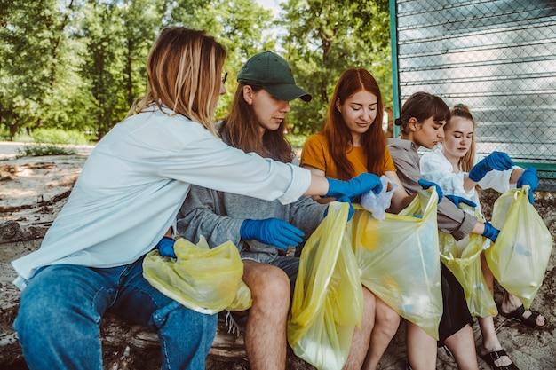 Группа активистов друзей, собирающих пластиковые отходы в парке. охрана окружающей среды.