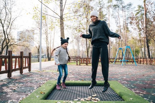 Мама и ее дочь прыгают вместе на батуте в осеннем парке