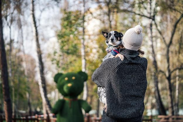 女の子が雑種犬を腕に抱えています。動物の世話をする。
