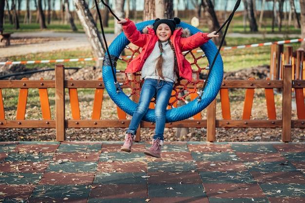 ブランコに乗って幸せな子供の女の子。秋のパックで遊ぶ子供。