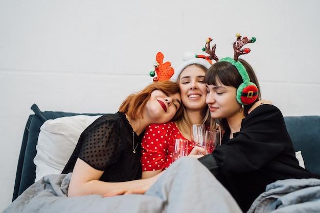 Улыбающиеся женщины, держащие бокалы и наслаждающиеся пижамной вечеринкой