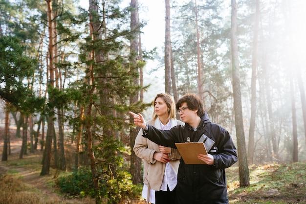 科学者たちは植物種を研究し、森の中の木を調べています。
